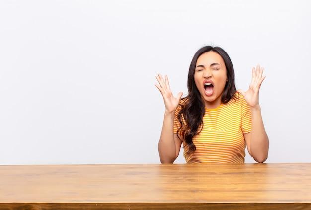 Jonge latijns-mooie vrouw woedend schreeuwen, gestrest en geïrriteerd voelen met handen omhoog in de lucht zeggen waarom ik over muur