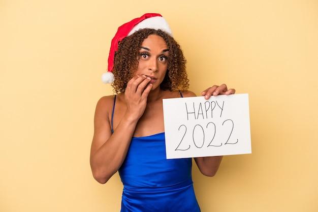 Jonge latijns-transseksuele vrouw die nieuwjaar viert geïsoleerd op gele achtergrond vingernagels bijten, nerveus en erg angstig.