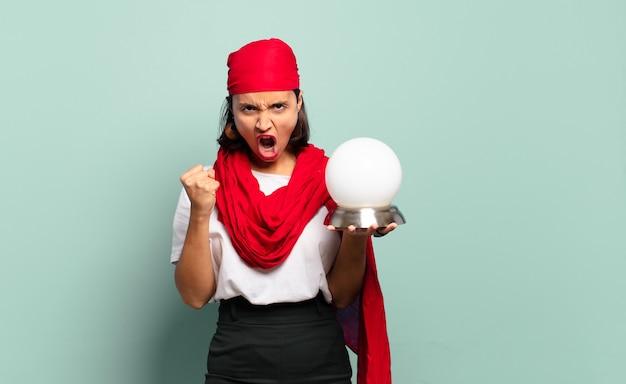 Jonge latijns-vrouw agressief schreeuwen met een boze uitdrukking of met gebalde vuisten het vieren van succes