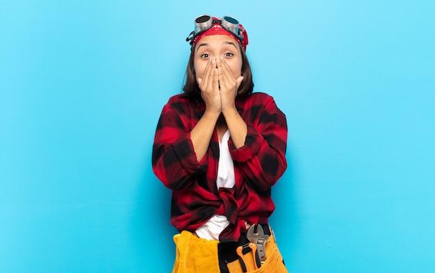 Jonge latijns-vrouw blij en opgewonden, verrast en verbaasd mond bedekt met handen, giechelend met een schattige uitdrukking