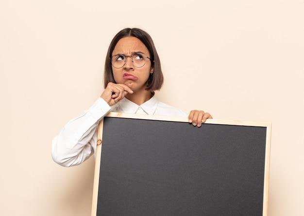 Jonge latijns-vrouw denken, twijfelachtig en verward voelen, met verschillende opties, zich afvragend welke beslissing ze moet nemen