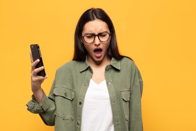 Jonge latijns-vrouw die agressief schreeuwt, er erg boos, gefrustreerd, verontwaardigd of geïrriteerd uitziet, nee schreeuwt