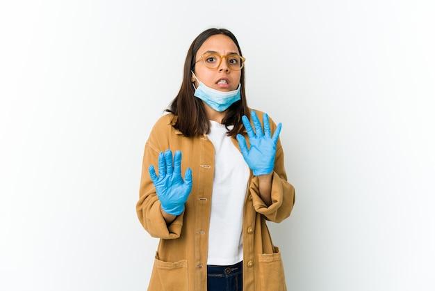 Jonge latijns-vrouw die een masker draagt om te beschermen tegen covid geïsoleerd op een witte achtergrond wordt geschokt als gevolg van een dreigend gevaar