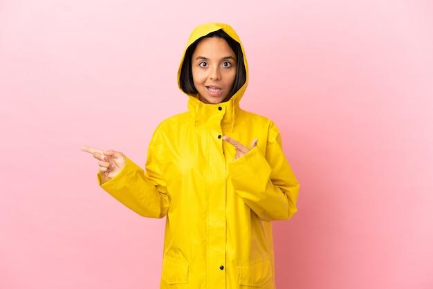 Jonge latijns-vrouw die een regenbestendige jas draagt over een geïsoleerde achtergrond, verrast en naar de zijkant wijst