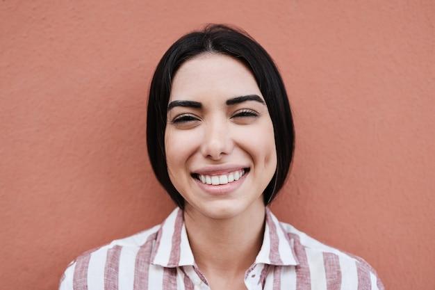 Jonge latijns-vrouw die lacht op camera buiten in de stad - focus op gezicht