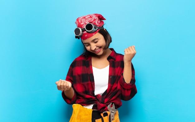 Jonge latijns-vrouw die lacht, zich onbezorgd, ontspannen en gelukkig voelt, danst en naar muziek luistert, plezier heeft op een feestje
