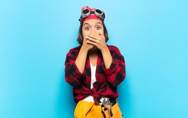 Jonge latijns-vrouw die mond bedekt met handen met een geschokte, verbaasde uitdrukking, een geheim bewaren of oeps zeggen