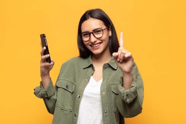 Jonge latijns-vrouw die trots en zelfverzekerd glimlacht en nummer één triomfantelijk laat poseren, zich een leider voelt