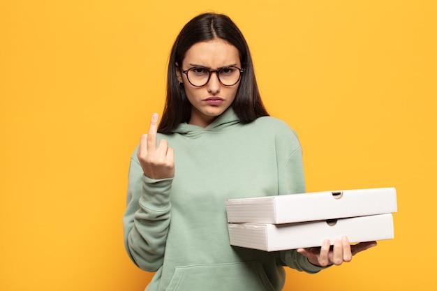 Jonge latijns-vrouw die zich boos, geïrriteerd, opstandig en agressief voelt, de middelvinger wegknipt