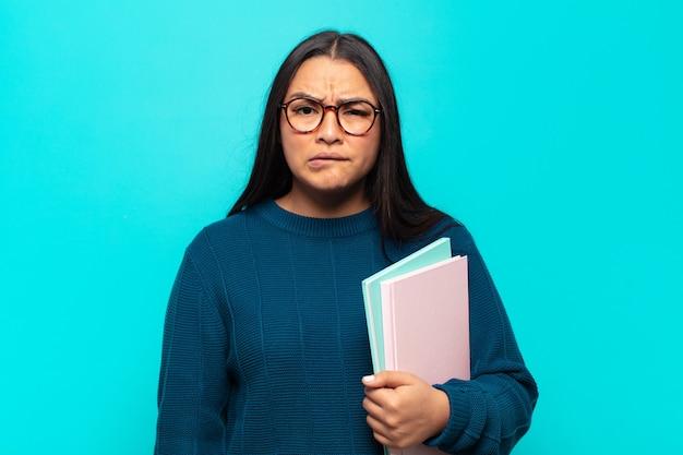 Jonge latijns-vrouw die zich geen idee, verward en onzeker voelt over welke optie ze moet kiezen, in een poging het probleem op te lossen