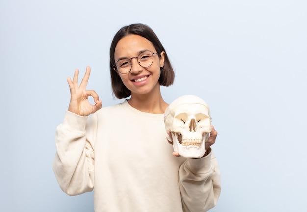 Jonge latijns-vrouw die zich gelukkig, ontspannen en tevreden voelt, goedkeuring toont met een goed gebaar, glimlachend