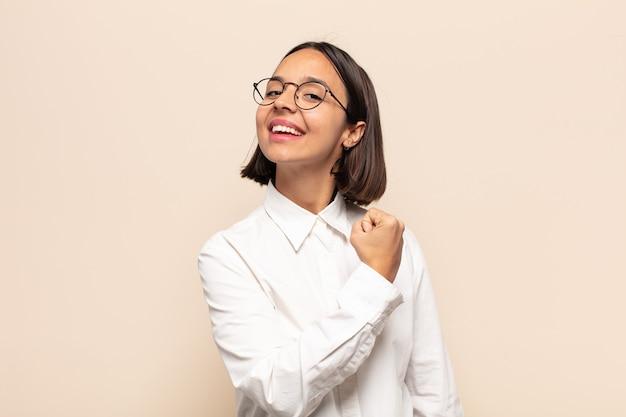 Jonge latijns-vrouw die zich gelukkig, positief en succesvol voelt, gemotiveerd wanneer ze voor een uitdaging staat of goede resultaten viert