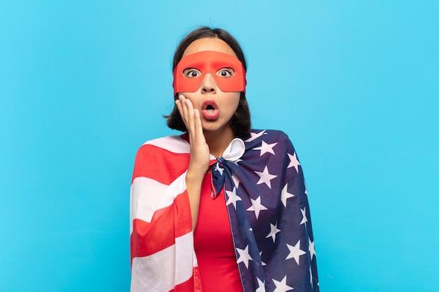 Jonge latijns-vrouw die zich geschokt en verbaasd voelt terwijl ze met wijd open mond ongeloof van aangezicht tot hand houdt