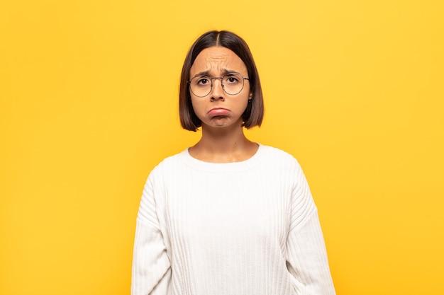 Jonge latijns-vrouw die zich verdrietig en gestrest voelt, van streek is vanwege een onaangename verrassing, met een negatieve, angstige blik Premium Foto