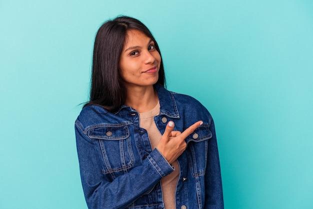 Jonge latijns-vrouw geïsoleerd op blauwe achtergrond glimlachend en opzij wijzend, iets tonen op lege ruimte.
