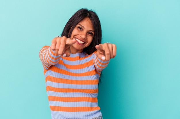 Jonge latijns-vrouw geïsoleerd op blauwe achtergrond naar voren wijzend met vingers.