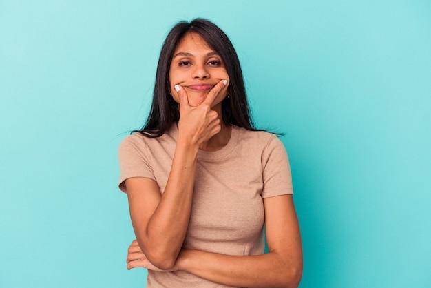 Jonge latijns-vrouw geïsoleerd op blauwe achtergrond twijfelen tussen twee opties.