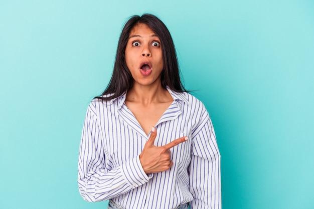 Jonge latijns-vrouw geïsoleerd op een blauwe achtergrond die naar de zijkant wijst