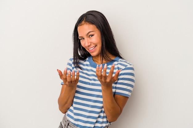 Jonge latijns-vrouw geïsoleerd op een witte achtergrond die met de vinger naar je wijst alsof uitnodigend dichterbij komt.