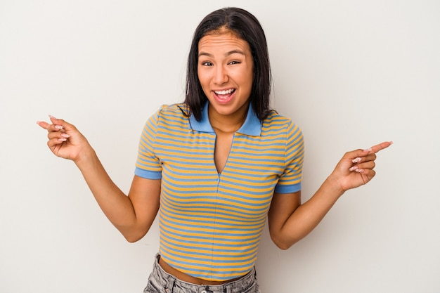 Jonge latijns-vrouw geïsoleerd op een witte achtergrond die naar verschillende kopieerruimten wijst, een van hen kiest en met de vinger laat zien.