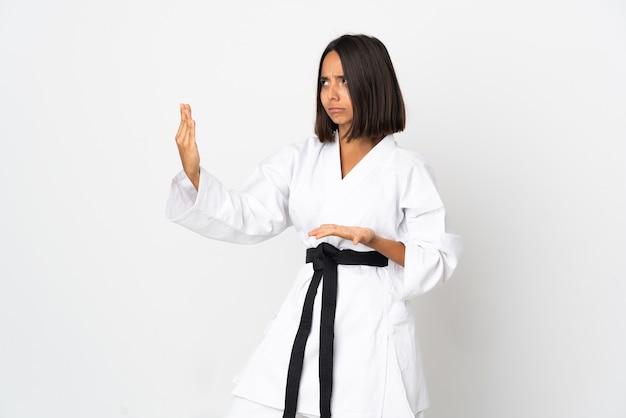 Jonge latijns-vrouw geïsoleerd op een witte achtergrond karate doen