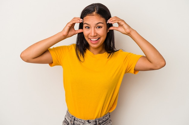 Jonge latijns-vrouw geïsoleerd op een witte achtergrond ontvangen van een aangename verrassing, opgewonden en handen opsteken.