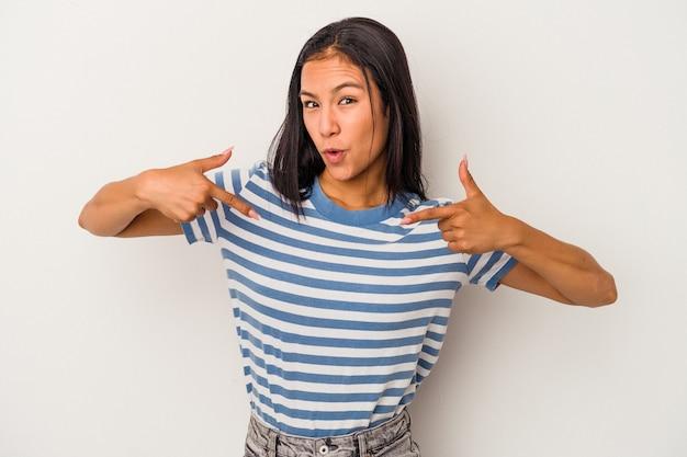 Jonge latijns-vrouw geïsoleerd op een witte achtergrond wijst naar beneden met vingers, positief gevoel.