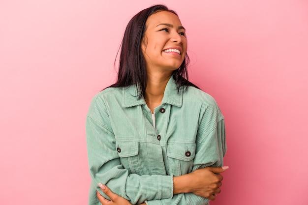 Jonge latijns-vrouw geïsoleerd op roze achtergrond glimlachend zelfverzekerd met gekruiste armen.