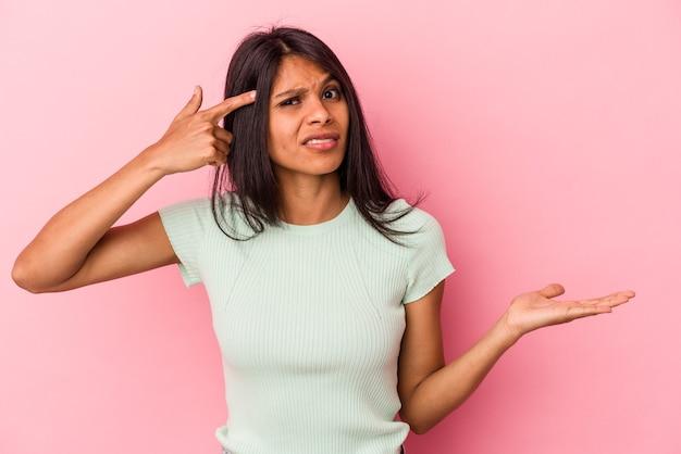 Jonge latijns-vrouw geïsoleerd op roze achtergrond houden en tonen van een product bij de hand.