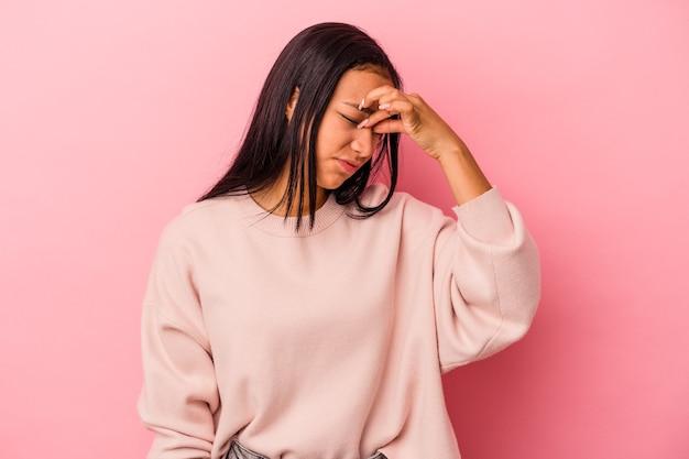 Jonge latijns-vrouw geïsoleerd op roze achtergrond met hoofdpijn, voorkant van het gezicht aan te raken.