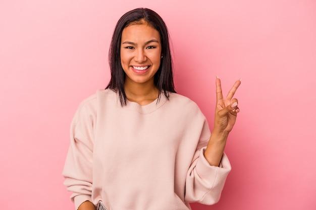 Jonge latijns-vrouw geïsoleerd op roze achtergrond met nummer twee met vingers.