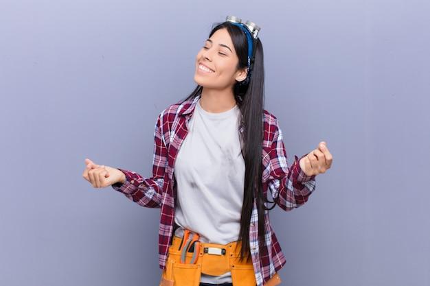 Jonge latijns-vrouw glimlachend, zorgeloos, ontspannen en gelukkig, dansen en luisteren naar muziek, plezier maken op een feestje
