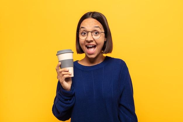 Jonge latijns-vrouw kijkt blij en aangenaam verrast, opgewonden met een gefascineerde en geschokte uitdrukking