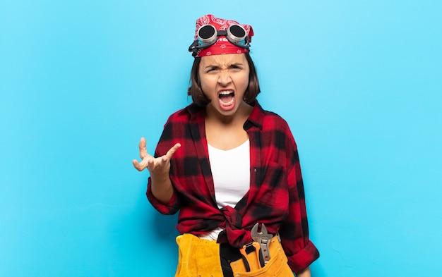 Jonge latijns-vrouw kijkt boos, geïrriteerd en gefrustreerd schreeuwend wtf of wat is er mis met je