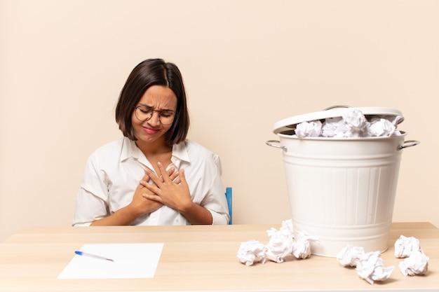 Jonge latijns-vrouw kijkt verdrietig, gekwetst en diepbedroefd, houdt beide handen dicht bij het hart, huilt en voelt zich depressief