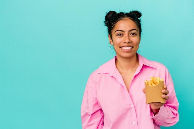 Jonge latijns-vrouw met chips geïsoleerd op blauwe achtergrond gelukkig, lachend en vrolijk.
