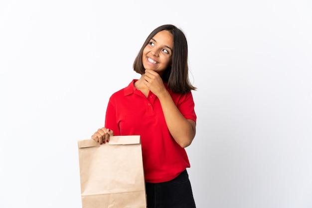 Jonge latijns-vrouw met een boodschappentas op een witte achtergrond