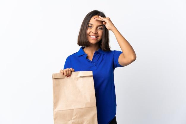 Jonge latijns-vrouw met een boodschappentas op wit wordt geïsoleerd groeten met de hand met gelukkige uitdrukking