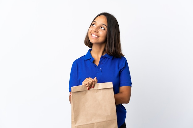 Jonge latijns-vrouw met een boodschappentas op wit wordt geïsoleerd opzoeken terwijl glimlachen
