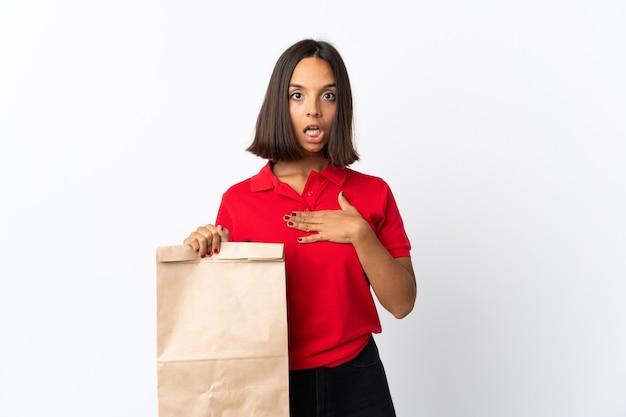 Jonge latijns-vrouw met een boodschappentas op wit wordt geïsoleerd verrast en geschokt terwijl ze naar rechts kijkt