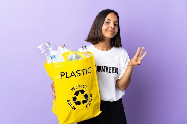 Jonge latijns-vrouw met een recycling zak vol papier om te recyclen geïsoleerd op paars blij en drie tellen met vingers
