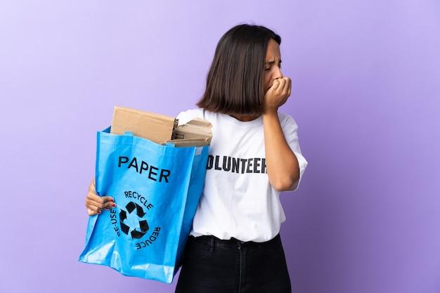 Jonge latijns-vrouw met een recycling zak vol papier om te recyclen geïsoleerd op paars met twijfels