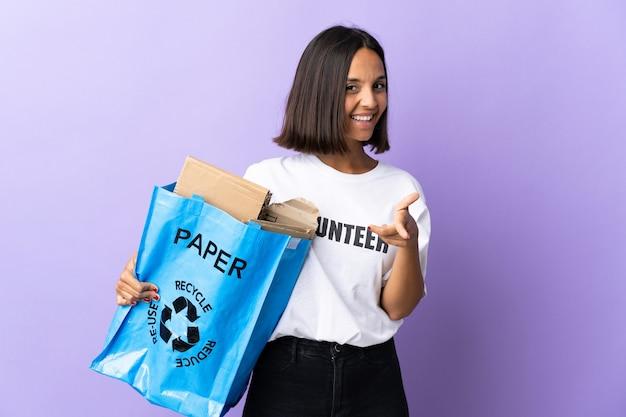 Jonge latijns-vrouw met een recycling zak vol papier om te recyclen geïsoleerd op paars naar voren wijzend en glimlachend