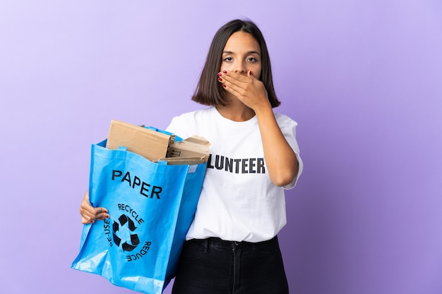 Jonge latijns-vrouw met een recycling zak vol papier om te recyclen geïsoleerd op paarse kegelvormige mond met hand