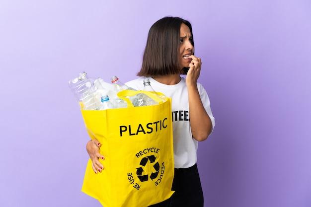 Jonge latijns-vrouw met een recyclingzak vol papier om te recyclen geïsoleerd op paars is een beetje nerveus