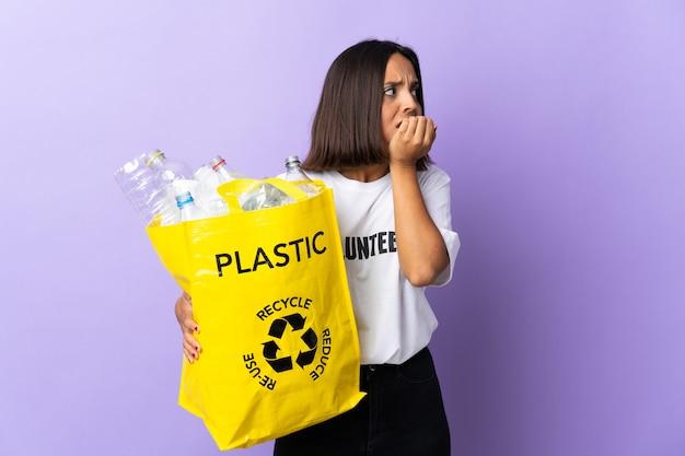 Jonge latijns-vrouw met een recyclingzak vol papier om te recyclen geïsoleerd op paars nerveus en bang handen op de mond