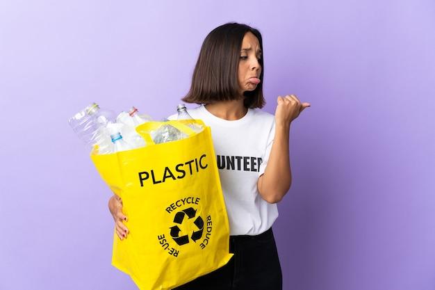 Jonge latijns-vrouw met een recyclingzak vol papier om te recyclen geïsoleerd op paars ongelukkig en wijst naar de zijkant