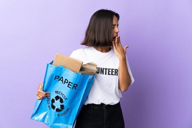 Jonge latijns-vrouw met een recyclingzak vol papier om te recyclen