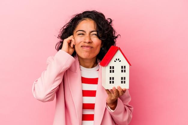 Jonge latijns-vrouw met een speelgoedhuis geïsoleerd op een roze achtergrond die oren bedekt met handen.
