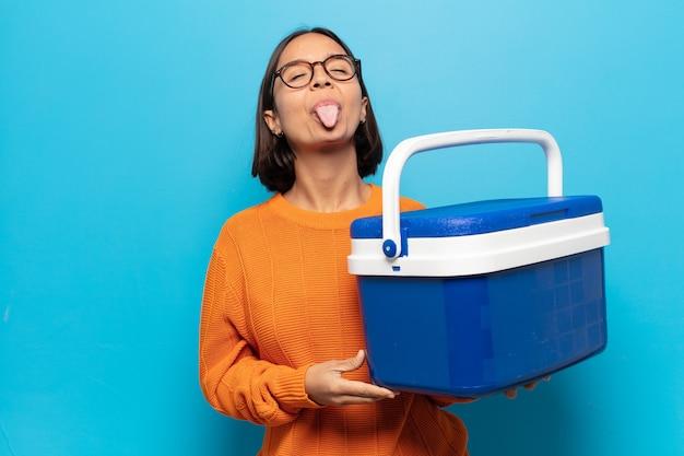 Jonge latijns-vrouw met vrolijke, zorgeloze, rebelse houding, grappen maken en tong uitsteken, plezier maken